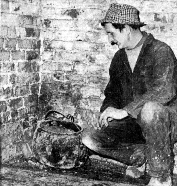 O sr. Alf darwood, de ulceby, o construtor encarregado de renovar a manor farm em east halton, examina o caldeirão amaldiçoado da casa em 1975.